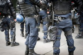 Members of a Swiss armed police squad wait to be deployed at a protest rally